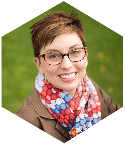 Photo of Dana wearing glasses and a scarf with honeycomb pattern and brown jacket