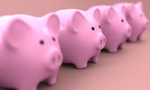 Four pink piggy banks in a row.