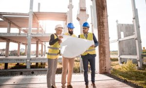 Three architects looking over a blueprint at a construction site