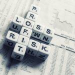 """Dice with letters spelling out """"profit"""", """"loss"""", and """"risk""""."""